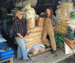 Two women stand in front of a stack of amendment bags