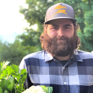 A man in a flannel shirt and blue and gold hat holding vegetables