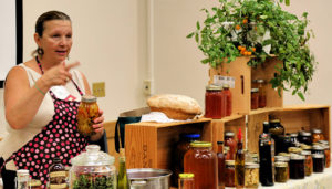 Woman teaching from behind a table filled with food and jars of food