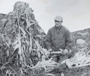 black and white photo of a man kneeling with corn and cornstalks