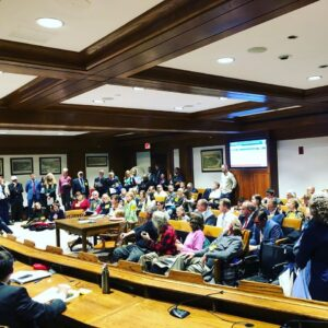 A room full of people seated for testimony at the Massachusetts state house.