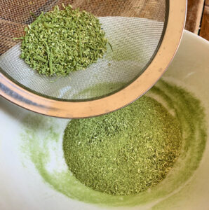 Green powder in a bowl with some being sifted through a mesh strainer