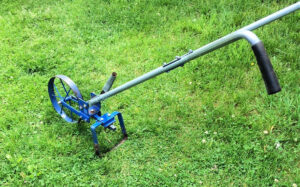 A long handled hoe with a wheel attachment